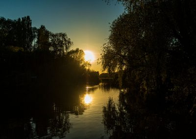 Great River Ouse sun setting into the river between the trees